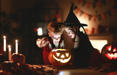 happy children in costumes of witch and vampire in a dark house in halloween. Fototapete