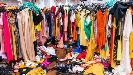 Messy clearance section in a clothing store, with colorful garments on racks and on the floor
