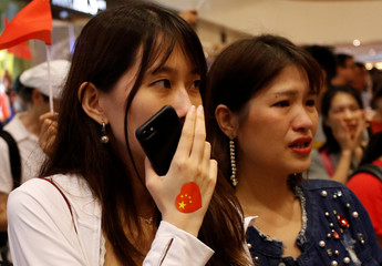 A pro-China supporter watches as another pro-China supporter is escorted out of a shopping mall by anti-government people after he waved the national flag of China, at Harbour City in Hong Kong
