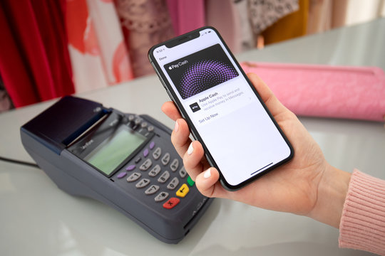 Woman holding iPhone with Apple Pay Cash and online terminal.