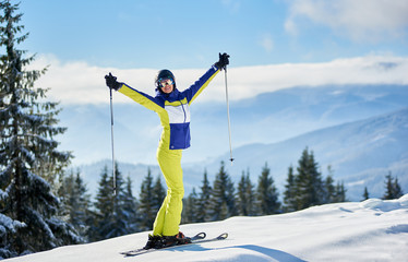 Smiling young woman in goggles posing on skis with hands up with ski poles on winter sunny day. Activity, thrill, victory, achievement concept. View of landscapes from mountain peak. Copy space.