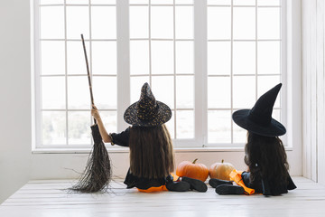 Girls in Halloween costumes with broom sitting near window