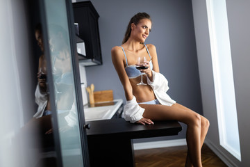 Sexy brunette female in white male shirt over lingerie holding red wine in a glass