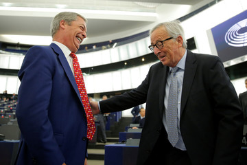 European Commission President Jean-Claude Juncker talks with Brexit Party leader Nigel Farage before a debate on Brexit at the European Parliament in Strasbourg