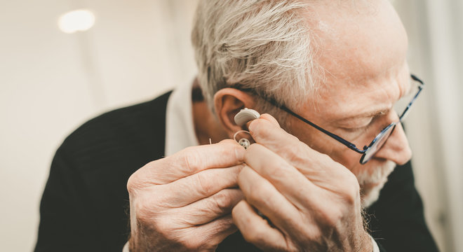 Man putting hearing aids