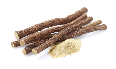 Licorice powder with licorice roots on white background