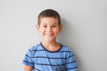 Portrait of happy little boy on light background
