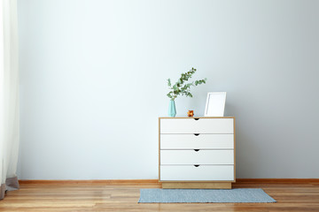 Chest of drawers with eucalyptus branches in vase near light wall