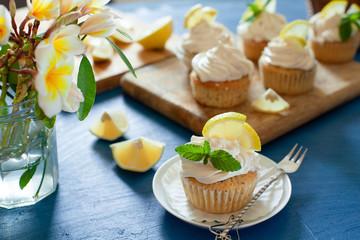 Lemon cupcakes with poppy seeds, white butter cream and  slice of lemon