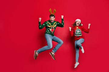 Full length photo of amazed lady and guy jumping excited by x-mas prices wear ugly ornament jumpers and headwear isolated red color background