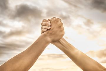 Hands shake. Unity, good sportsmanship, and teamwork.