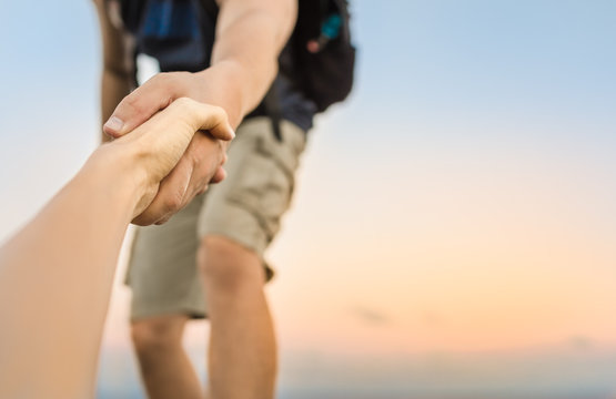 Hikers climbing mountain, helping, giving hand to friend.
