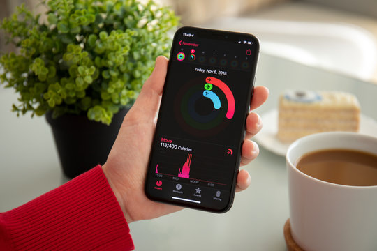 Woman hand holding iPhone X with app Activity