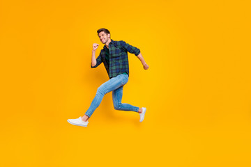 Full length body size side profile photo of cheerful positive funny trendy guy wearing jeans denim hurrying jumping up to sales isolated over vivid color yellow background