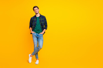 Full length body size photo of cheerful charming cute handsome man posing in front of camera with hands in pockets isolated over vivid color background