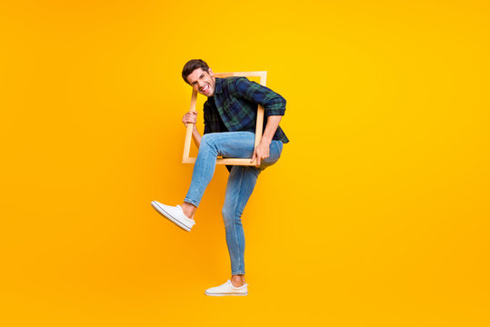 Full length photo of crazy guy holding wooden picture frame putting leg inside it wear casual checkered shirt and jeans isolated yellow color background