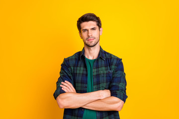Photo of amazing macho guy with crossed hands watching how colleagues working wear casual plaid shirt isolated yellow color background
