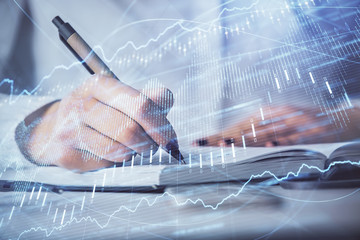 Multi exposure of woman's hands making notes with forex graph hologram. Concept stock market analysis.