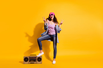 Full body photo of funky lady with big tape recorder showing v-sign symbols wear casual trendy clothes isolated yellow color background