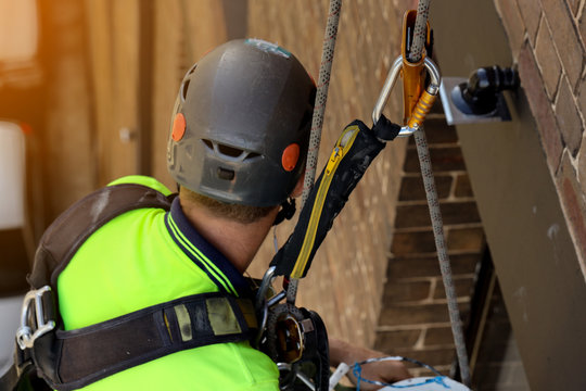 Industrial rope access abseiler wearing full body safety harness resting hanging in fall arrest, maintenance fall arrester shock energy absorbing lanyard backup device safe distance fall factor one