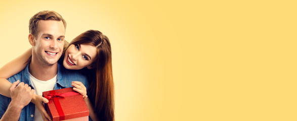 Photo of lovely couple with gift box, over yellow color background