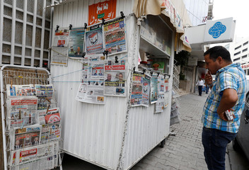 A man looks at local newspapers displaying pictures of two candidates for the second round of Tunisia's presidential election, in Tunis