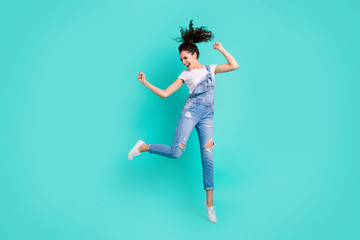 Full length body size view of her she nice attractive lovely cheerful cheery girl wearing blue overall jumping having fun isolated over bright vivid shine vibrant green turquoise background Wall mural