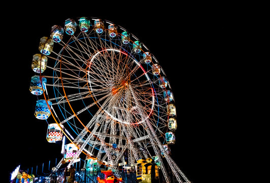 Giant Ferris Wheel with well illuminated cabins and decorated with colorful lights during night, is up for the entertainment, in a local festival in Goa during summers.