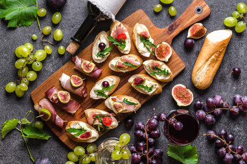 Traditional tapas bar, spanish table with food, platter with appetizers or italian bruschetta with cheese and meat. Wine snack set