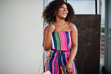 Fashionable african american woman in pink striped jumpsuit, with handbag posed and laughing loudly.