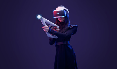 Wall Mural - Beautiful woman in futuristic dress over dark background. Gamer girl in glasses of virtual reality with controller in hands. Augmented reality, game, hobby concept. VR.