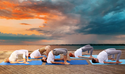 fitness, sport, yoga and healthy lifestyle concept - group of people making bridge pose on sea pier over sunset background