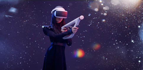 Wall Mural - Beautiful woman in futuristic dress over dark blue magic light background. Gamer girl in glasses of virtual reality with controller in hands. Augmented reality, game, hobby concept. VR.