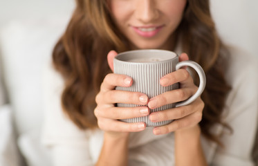 Fototapete - drink, christmas and hygge concept - close up of happy woman with cup of coffee at home