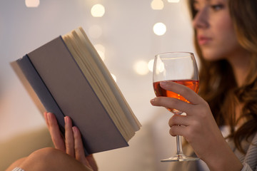 Fototapete - christmas, leisure and comfort concept - close up of young woman reading book and drinking rose wine from glass