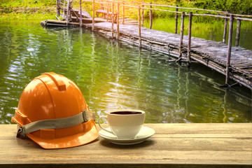 Architect work space outdoor on nature , orange safety hard hat with  coffee cup  on wooden table., Architect concept,