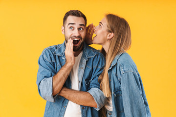 Image of happy woman whispering secret to excited man in his ear