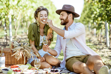 Beautiful couple having romantic breakfast with lots of tasty food and wine, sitting together on the picnic blanket at the vineyard on a sunny morning Fototapete