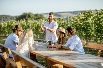 Spoed Fotobehang Wijngaard Group of a young people drinking wine and talking together while sitting at the dining table outdoors on the vineyard on a sunny evening