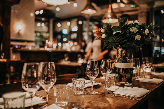 Elegant table set up for a romantic dinner. Concept of catering, hospitality and private dining. Selective focus on the glassware.