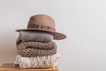 Pile of warm knitted woolen winter sweates and felt hat