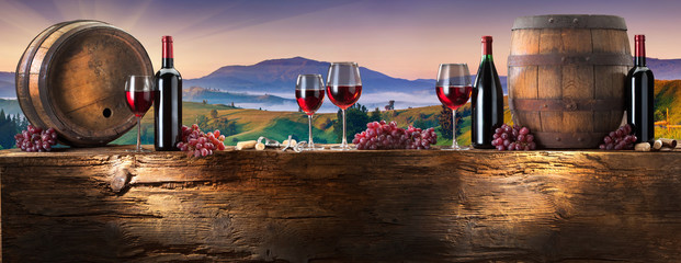 Photo sur Aluminium Alcool red wine on an old wood with a landscape background