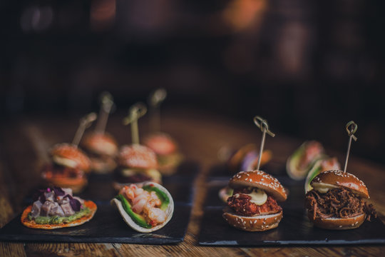 A close up shot of a selection of canape dishes. Concept of catering, hospitality and lifestyle. Small snacks and nibbles served on black slates for a private reception.