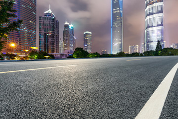 Shanghai modern commercial buildings and asphalt highway at night,China.