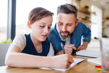 Wall Mural - Mature father with small son sitting at table indoors, doing homework.
