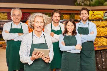 Marktleiterin vor ihrem Supermarkt Team
