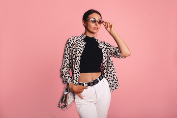 Fashion photo of a beautiful young woman in a casual summer look with animal print shirt, bag and white jeans posing over pink background. Fashion photo, copy space