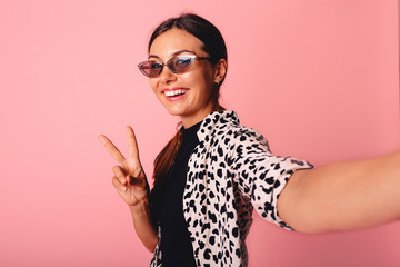 Image of charming young woman smiling and taking selfie photo isolated over yellow background.Lovely playful young woman taking selfie with mobile phone