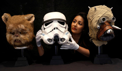 An employee of Prop Store poses for a photograph with an Ewok mask, a Stormtroopers' helmet and a prototype of a Tusken Raider mask at a preview of a film and tv memorabilia sale in London