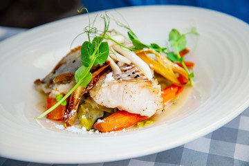 Delicious fillet of cod fish with carrots, leeks and mushrooms in white plate ready to be served
